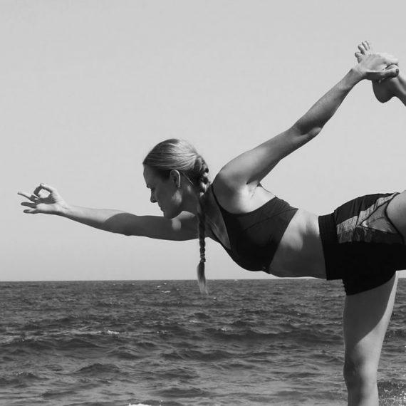 Imagen en blanco y negro de Marieke haciendo yoga al borde del mar