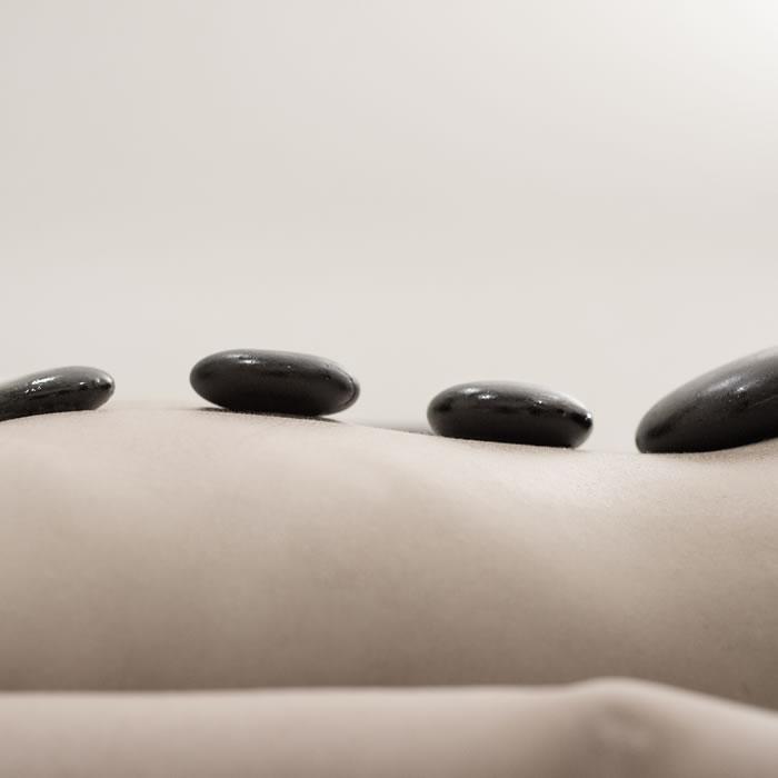 Imagen de una persona tumbado, solo se ve la espalda con piedras colocado por la columna dorsal